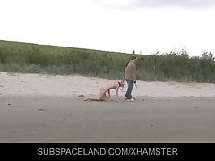 Slim blonde slave leashed and whipped on the beach